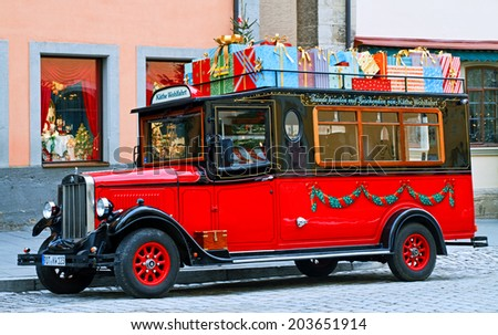 Rothenburg ob der Tauber - January 04: Red old-fashioned car with christmas presents in front of world famous Christmas Kathe Wohlfahrt Store on January 04, 2014 in Rothenburg ob der Tauber, Germany. - stock photo