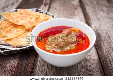 roti canai with spicy curry on old wood background - stock photo