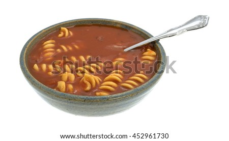Rotini tomato soup in an old stoneware bowl with a spoon inserted into the food isolated on a white background. - stock photo