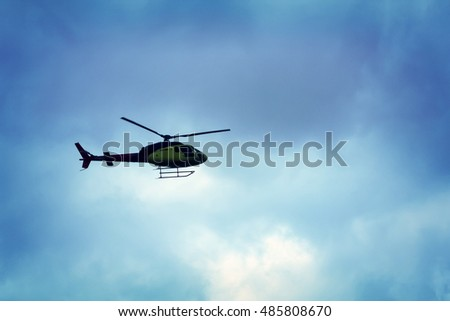 Rotor helicopter flying against the blue sky background