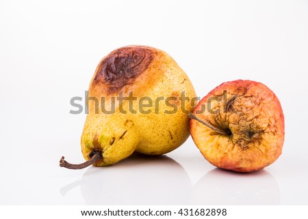 Rotten and decomposing organic red apple and pear on white background