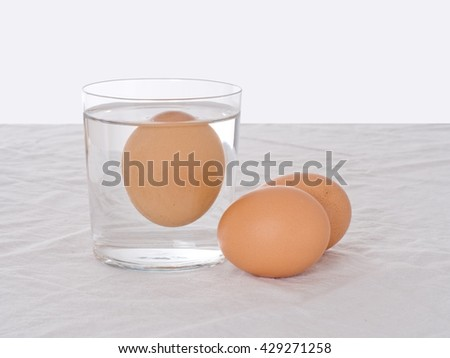 Rotten egg, salmonella risk. Old fashioned test. Bad egg floats in glass of water. - stock photo