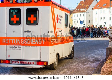 Rottenburg am Neckar, Germany - February 26, 2017: German ambulance car, costumed people in the background after a traditional carnival parade