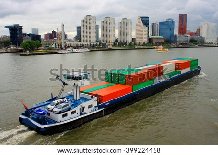 Rotterdam, august 18. 2015: Large Cargo ship in Rotterdam harbor with cityscape in the back. - stock photo