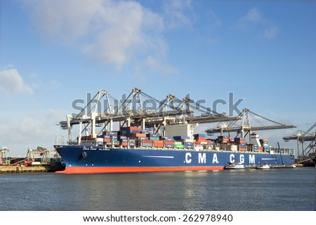 ROTTERDAM - JAN 13, 2012: Gantry crane placing a container in a cargo ship the Port of Rotterdam. The port is the Europ's largest and facilitate the needs of a hinterland with 40,000,000 consumers. - stock photo