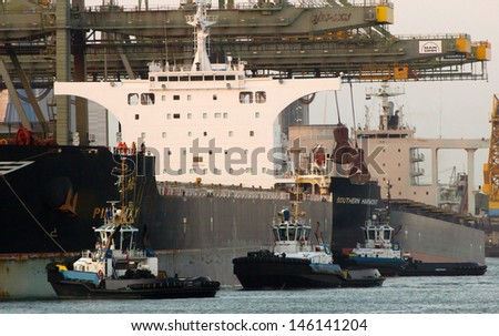 ROTTERDAM - JULY 08: Tugboats assisting a bulkcarrier on July 08, 2013 in Rotterdam, Holland. The port of Rotterdam plays a main role in the international transfer and transit of ore deposits  - stock photo