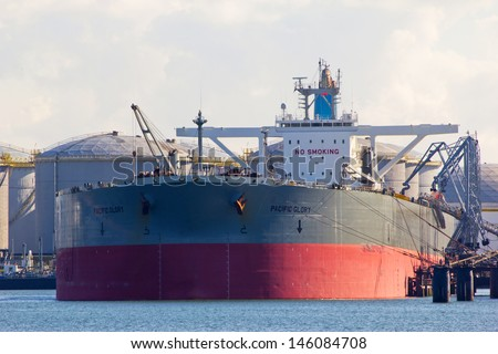 ROTTERDAM - MARCH 19: A supertanker docking on March 19, 2012 in Rotterdam, Holland. The port of Rotterdam plays a dominant role in the international transfer and refinement of crude oil  - stock photo