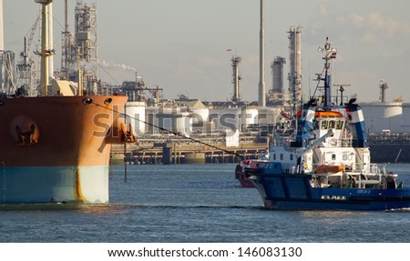 ROTTERDAM - MARCH 19: A tugboat assists a tanker on March 19, 2012 in Rotterdam, Holland. The port of Rotterdam plays a dominant role in the international transfer and refinement of crude oil  - stock photo