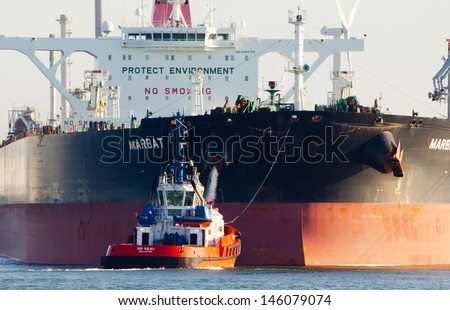ROTTERDAM - MARCH 19: Tugboats asisting the supertanker 'Marbat' on March 19, 2012 in Rotterdam, Holland. The 'Marbat' (320,000 dwt) is the first of a new series of very large crude carriers (VLCC) - stock photo