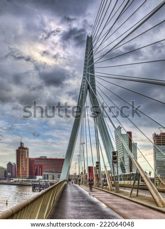 ROTTERDAM,NETHERLANDS- APR 24:Image of few people cycling on the Erasmus Bridge during a rainy day on April 24, 2012 in Rotterdam.This bridge links the northern and southern regions of the city - stock photo