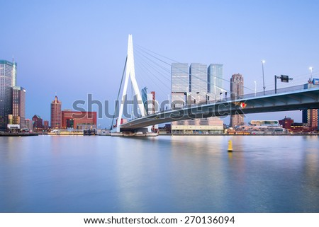 ROTTERDAM, NETHERLANDS - APRIL 6: Skyline of city at dusk, with the Erasmus Bridge illuminated in the blue hour at dusk, reflections in the river water, on April 6, 2015, in Rotterdam, Netherlands, - stock photo
