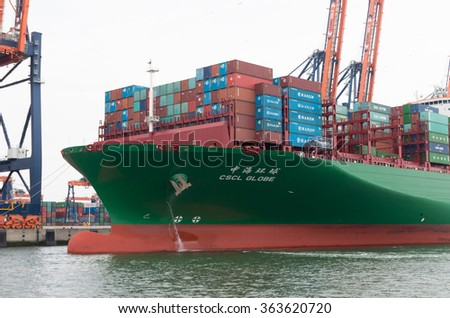 ROTTERDAM, NETHERLANDS - JUNE 28, 2015: CSCL Globe container ship mooring in the Rotterdam harbor. The CSCL Globe measures 400 meters in length, 58.6 meters in width and 30.5 meters in depth. - stock photo