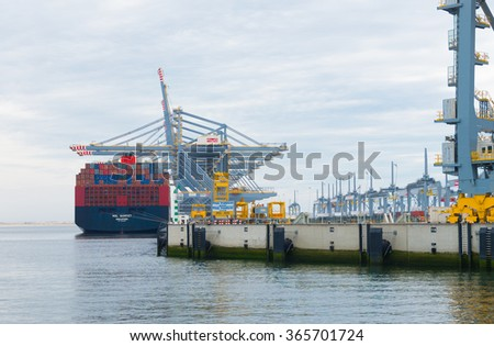 ROTTERDAM, NETHERLANDS - JUNE 28, 2015: Large harbor cranes loading a container ship. Rotterdam is the largest harbor in Europe. - stock photo
