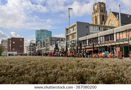Rotterdam, Netherlands - March 7, 2015: People visit shops near the Grotekerk (Big church) in Rotterdam. Rotterdam is a city with a fascinating contrast between old and new styles of architecture.