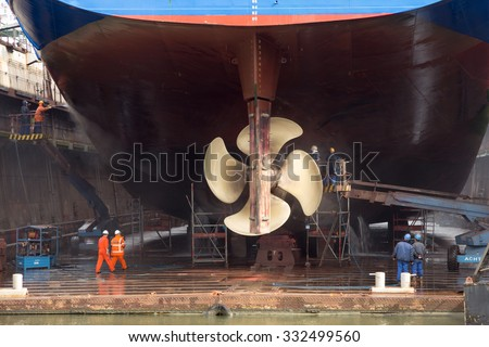 ROTTERDAM, NETHERLANDS - SEP 5, 2015: Workers removing algue in ship repair dry dock. - stock photo