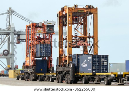 ROTTERDAM, NETHERLANDS - SEPTEMBER 8, 2013: Straddle carriers moving shipping containers in the Port of Rotterdam.  - stock photo