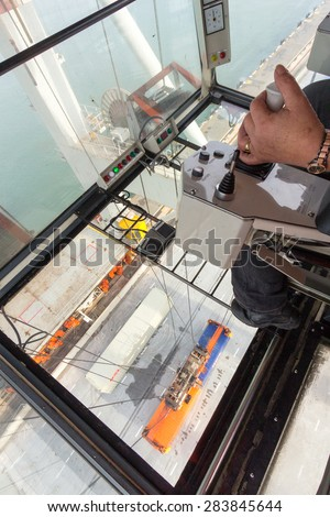 ROTTERDAM - SEP 8, 2013: Container crane operator in the Port of Rotterdam, Netherlands. The port is the Europ's largest and facilitate the needs of a hinterland with 40,000,000 consumers.  - stock photo