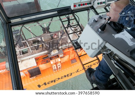 ROTTERDAM - SEP 9, 2015: Gantry crane operator moving a sea container in the Port of Rotterdam. - stock photo
