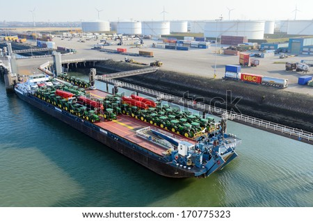 ROTTERDAM, SOUTH HOLLAND, NETHERLANDS - MARCH 28: Tractors loaded onto cargo barge in the Port of Rotterdam on March 28, 2013 in Rotterdam, South Holland, Netherlands.