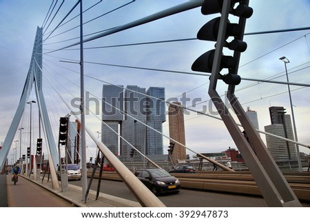 ROTTERDAM, THE NETHERLANDS - 18 AUGUST: Cars traffic driving and bicyclists crossing on the Erasmus bridge (Erasmusbrug) in Rotterdam, Netherlands on August 18,2015.