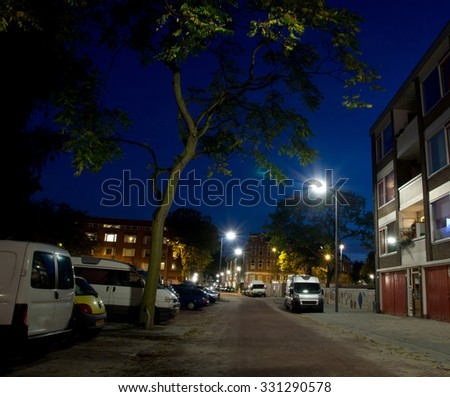 ROTTERDAM, THE NETHERLANDS - OCTOBER 09, 2012: Parked cars by apartment buildings in the night - stock photo