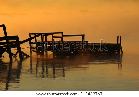 Rotting pier is surrounded by the golden light of dawn on Lake Chicot in Lake Village, Arkansas.