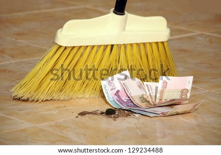 Roubles banknotes and garbage are being swept with a broom. - stock photo