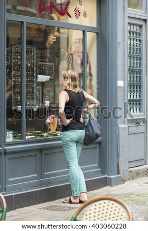 ROUEN, FRANCE - JULY 2, 2015: A young woman observes a showcase of jewelry, in one of the streets of the old town. - stock photo
