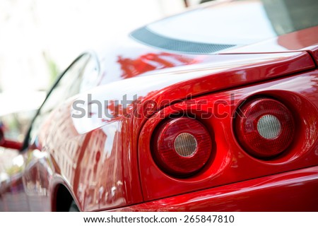 ROUEN, FRANCE - JUNE 23: Beautiful bright red Ferrari parked on downtown Rouen street in June 23, 2012. Close up of Ferrari tail lights. - stock photo