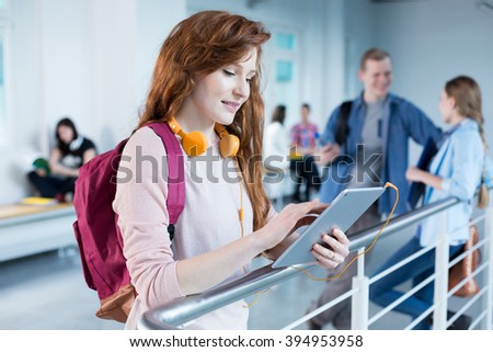 Rouge student with colorful headphones, rucksack and digital tablet - stock photo