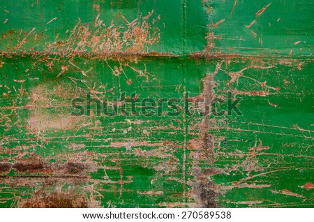Rough and battered green paint texture on a rusted metal surface showing scratches, dents and rust patches - stock photo