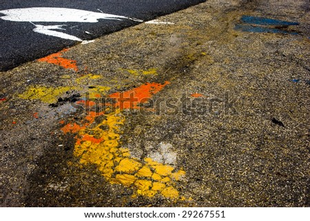 Rough asphalt with paint spatter. - stock photo