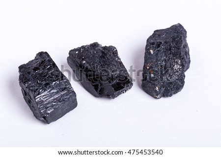 Rough black tourmaline rocks with natural shadows on the white background