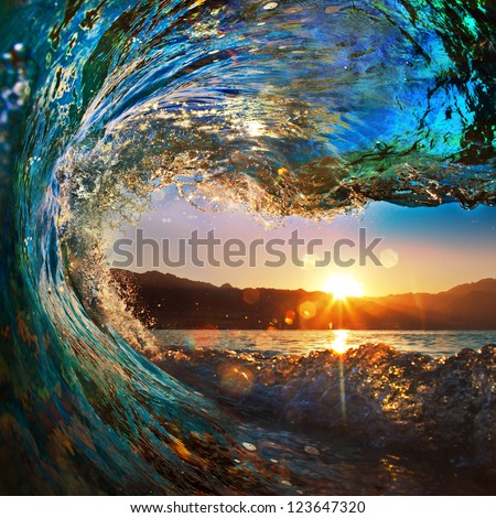 rough colored ocean wave falling down at sunset time - stock photo