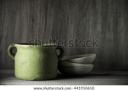 Rough handmade ceramic pot and bowls against rustic wooden wall. Low key. - stock photo