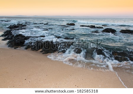 Rough sea and golden sand at the rugged coast in South Africa - stock photo
