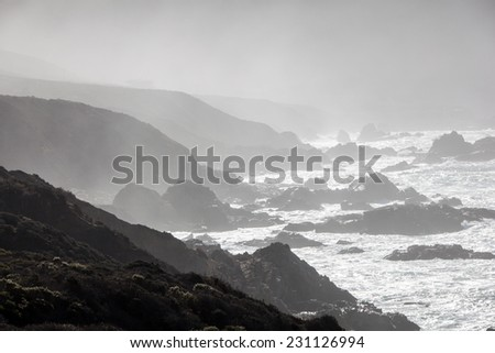 Rough seas wash against the rocky coast of Big Sur in California. This natural scenery along this part of the Pacific coastline is incredibly beautiful and dramatic. - stock photo