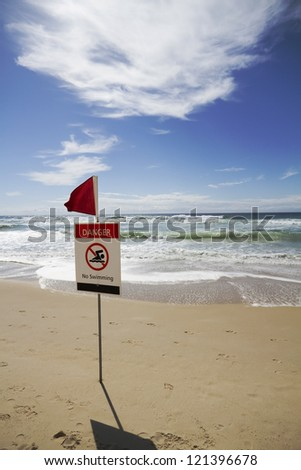 Rough surf beach at surfers paradise australia with danger sign - stock photo