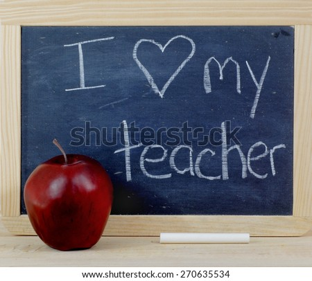 Rough textured blackboard with wooden frame. A red apple and a stick of white chalk sit in front. The black slate has a used or worn appearance. Horizontal composition. Message for teachers' day - stock photo