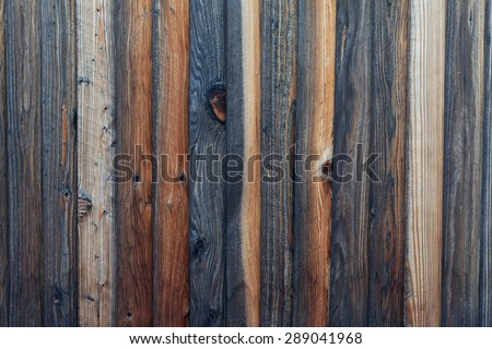 Rough textured wood plank fence. Wood panels show various colors and stages of weathering, from darker, medium browns to light colored sections. Horizontal background image. - stock photo