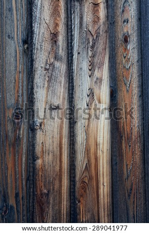 Rough textured wood plank fence. Wood panels show various colors and stages of weathering, from darker, medium browns to light colored sections. Vertical background image.