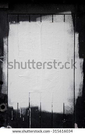 Rough white paint rolled over a black wooden textured background - stock photo
