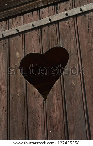 Rough wooden door with cut out Heart shape