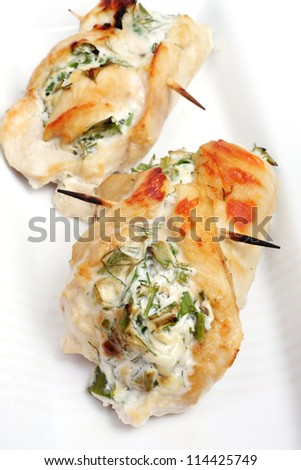 roulade of chicken breast with cheese and herbs, over white