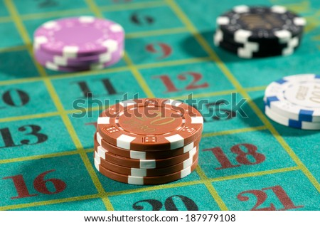 Roulette betting with casino chips placed on a series of numbers choosing either odds or evens and red or black - stock photo