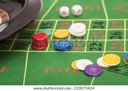 Roulette in casino ,chips and dices stacking on a green felt  - stock photo