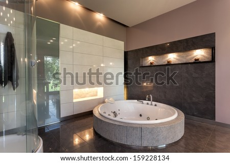 Round bath in a luxury tiled bathroom interior - stock photo