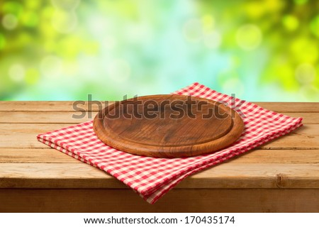 Round board on tablecloth on wooden table over bokeh background. Ready for product montage display - stock photo