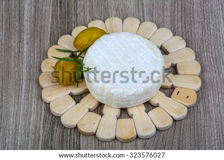 Round Brie cheese with yellow plums and estragon