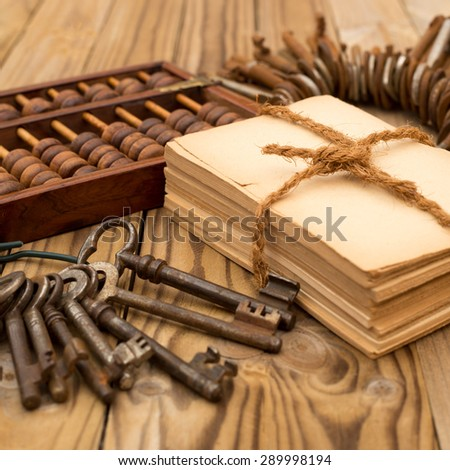 Round bunch of old weathered metal rusty vintage door keys, Tied with brown twine bundle of old yellowed paper, vintage brown wooden abacus on  old rustic wooden table background  - stock photo
